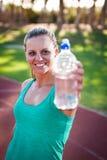 Atleta fêmea que guarda uma garrafa de água imagem de stock