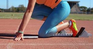 Atleta fêmea que toma a posição começar sobre a pista de atletismo 4k vídeos de arquivo