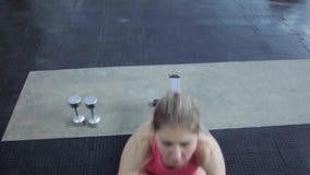 Atleta fêmea que trabalha em seu corpo no gym A menina é acoplada na aptidão filme