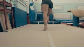 Atleta f?mea que exercita no gym, correndo acima e fazendo um salto mortal dobro para tr?s video estoque