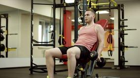 Atleta farpado que levanta os pesos e que trabalha seu bíceps no banco no gym filme