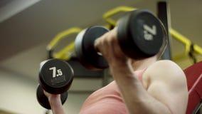 Atleta farpado que levanta os pesos e que trabalha seu bíceps no banco no gym, close-up vídeos de arquivo