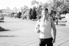 Atleta feliz do homem que sorri com a garrafa da água Imagens de Stock