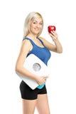 Atleta feliz que sostiene una escala del peso y una manzana roja Fotos de archivo libres de regalías