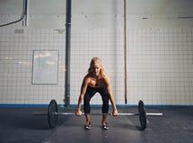 Atleta femminile adatto che esegue un deadlift Immagine Stock