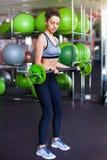 Atleta femminile adatto che fa sollevamento del peso massimo Immagine Stock