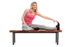Atleta femminile allegro che allunga la sua gamba Immagini Stock