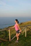 Atleta femminile che allunga dopo avere corso e l'esercitazione Immagine Stock Libera da Diritti