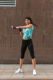 Atleta femminile che allunga il suo braccio La giovane donna che fa il riscaldamento si esercita prima di correre sulla pavimenta Fotografia Stock