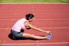 Atleta femminile che allunga il suo tendine del ginocchio Fotografia Stock Libera da Diritti