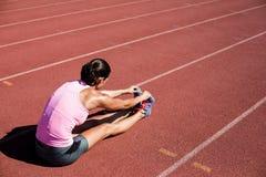 Atleta femminile che allunga il suo tendine del ginocchio Fotografie Stock Libere da Diritti