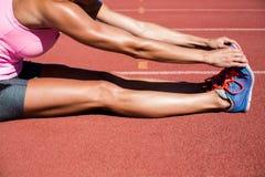 Atleta femminile che allunga il suo tendine del ginocchio Immagini Stock Libere da Diritti