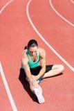 Atleta femminile che allunga il suo tendine del ginocchio Immagine Stock Libera da Diritti