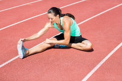 Atleta femminile che allunga il suo tendine del ginocchio Immagine Stock