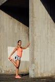 Atleta femminile che allunga le gambe per correre Immagini Stock