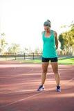 Atleta femminile che allunga su una pista corrente Fotografia Stock