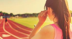 Atleta femminile che ascolta la musica su una pista corrente Fotografie Stock