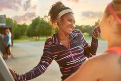 Atleta femminile che ascolta le cuffie mentre allungando prima dell'andare a correre all'aperto Immagine Stock