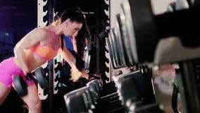 Atleta femminile che fa esercizio con una testa di legno nella palestra Nel riflettore archivi video
