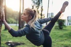 Atleta femminile che fa posa della tenuta della gamba che allunga esercizio che sta su una gamba nel parco della città Fotografia Stock