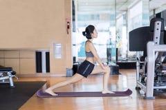 Atleta femminile che fa un allungamento sul centro di forma fisica Fotografia Stock Libera da Diritti