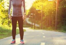 Atleta femminile che prepara per un trotto su un sentiero nel bosco fotografie stock