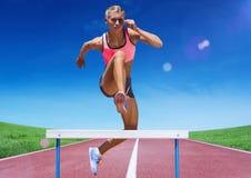 Atleta femminile che salta sopra la transenna sulla pista di corsa Fotografie Stock