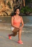 Atleta femminile che si scalda e che allunga alla spiaggia Immagini Stock