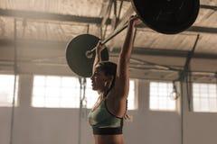 Atleta femminile che solleva i pesi pesanti Immagini Stock