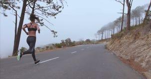 Atleta femminile che sprinta sulla strada principale della campagna video d archivio
