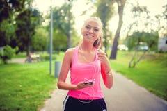 Atleta femminile di forma fisica che gode di un allenamento corrente in parco Fotografie Stock