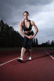 Atleta femminile di stirata del tendine del ginocchio sulla pista corrente Immagini Stock