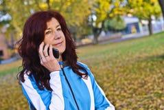 Atleta femminile emozionante che per mezzo del telefono Fotografia Stock Libera da Diritti