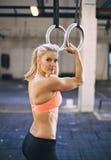 Atleta femminile muscolare che si esercita con gli anelli della ginnasta Fotografie Stock Libere da Diritti
