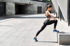 Atleta femminile sicuro di sé che si scalda il suo corpo Immagine Stock