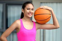 Atleta femminile Smiling With Basketball di minoranza graziosa immagini stock