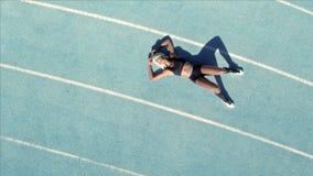 Atleta femminile stanco che riposa sulla pista stock footage