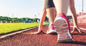 Atleta femminile sulla linea di partenza di pista dello stadio Immagini Stock