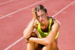 Atleta femminile turbato che si siede sulla pista corrente Fotografie Stock