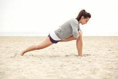Atleta fêmea Doing Stretching Exercise na praia Foto de Stock Royalty Free