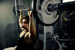 Atleta fuerte del culturista con los pesos pesados en gimnasio Foto de archivo libre de regalías