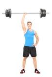 Atleta fuerte que lleva a cabo un peso en una mano Fotografía de archivo libre de regalías