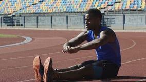 Atleta fuerte que se sienta en la pista corriente que hace ejercicios del calentamiento y de la flexibilidad almacen de metraje de vídeo