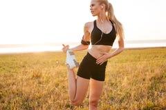 Atleta grazioso della giovane donna che fa allungando gli esercizi Fotografia Stock Libera da Diritti