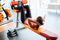 Atleta hermoso de la mujer que hace crujidos abdominales en banco en gimnasio Imagen de archivo libre de regalías