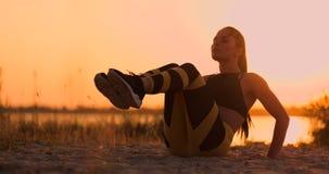 Atleta hermoso joven de la mujer que practica en la playa que hace los ejercicios para los músculos del ABS en la puesta del sol  almacen de metraje de vídeo