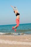 Atleta hermoso joven de la mujer que salta en la playa Imágenes de archivo libres de regalías