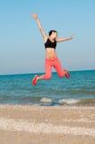 Atleta hermoso joven de la mujer que salta en la playa Fotos de archivo