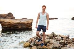 Atleta hermoso joven del hombre que se coloca en la playa rocosa Foto de archivo libre de regalías