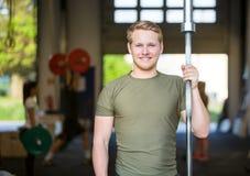 Atleta Holding Weightlifting Bar no Gym foto de stock